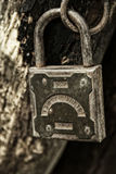 Old padlock hanging on the rotting jamb close up. Old padlock hanging on the rotting jamb Stock Image