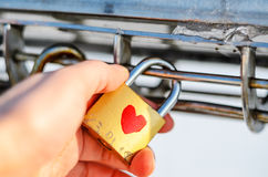 Old padlock with heart pattern on the palm Stock Photography