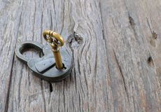 Old padlock and key on a wooden table. Royalty Free Stock Image