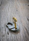 Old padlock and key on a wooden table. Royalty Free Stock Photo