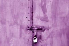 Old padlock on metal gate in purple tone. Royalty Free Stock Image