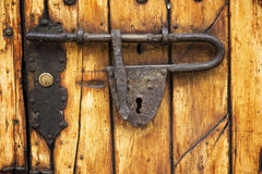 Old padlock in wood door. Detail of an ancient iron padlock on a wood door in Bogotá,Colombia Royalty Free Stock Image