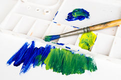 Old paint brush and palette. With blue and yellow painting Royalty Free Stock Photo