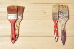 Old paint brushes on a wooden background. Old paint brushes in paint on a wooden background Royalty Free Stock Images