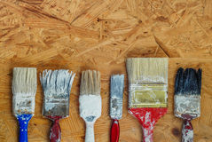 Old paint brushes on pressed wooden panel Royalty Free Stock Photos