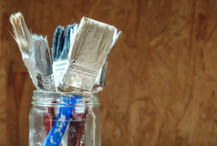 Old paint brushes on pressed wooden panel background Royalty Free Stock Photo