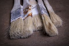 Old paint brushes on wood board background stock image