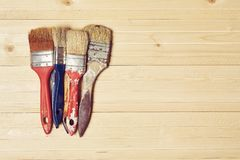 Old paint brushes on a wooden background. Old paint brushes in paint on a wooden background Stock Photos