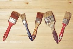 Old paint brushes on a wooden background. Old paint brushes in paint on a wooden background Stock Image