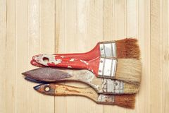 Old paint brushes on a wooden background. Old paint brushes in paint on a wooden background Stock Photo