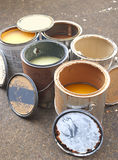 Old Paint in Metal, Rusty Cans Ready for Recycling. Vertical of old paint cans opened with various colors, all sitting on concrete slab royalty free stock images