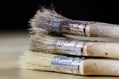 Old paintbrushes for paint, Cans of paint on wooden table. Paint. Ing workshop. Black background stock images