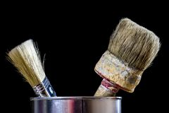 Old paintbrushes for paint, Cans of paint on wooden table. Paint. Ing workshop. Black background royalty free stock photos