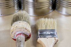 Old paintbrushes for paint, Cans of paint on wooden table. Paint. Ing workshop. Black background royalty free stock images
