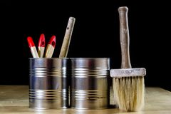 Old paintbrushes for paint, Cans of paint on wooden table. Paint. Ing workshop. Black background stock photos