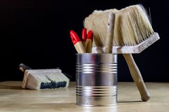 Old paintbrushes for paint, Cans of paint on wooden table. Paint. Ing workshop. Black background royalty free stock photo