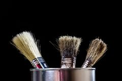 Old paintbrushes for paint, Cans of paint on wooden table. Paint. Ing workshop. Black background royalty free stock photography