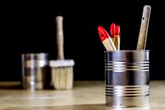 Old paintbrushes for paint, Cans of paint on wooden table. Paint. Ing workshop. Black background stock image