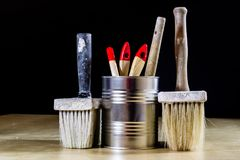 Old paintbrushes for paint, Cans of paint on wooden table. Paint. Ing workshop. Black background royalty free stock image