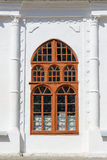Old painted arched window. In white brick wall Stock Photo