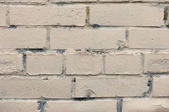Old painted beige color weathered stained brick wall stock image