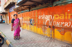 Old painted colorful walls of street and woman walking past Stock Image