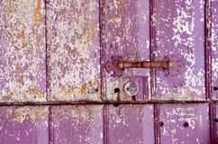 Old painted, crumbled door. Background of an old painted, crumbled door. Handle on purple wooden planks Stock Photos