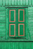 Old painted green wooden shuttered window on decorated wall.  Stock Photos