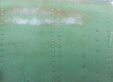 Old painted metal background detail of a military aircraft, surface corrosion. Royalty Free Stock Image