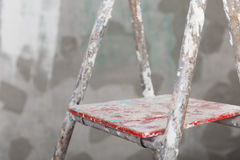Old painted and stucco ladder on concrete wall background Royalty Free Stock Images