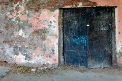Old painted wall  with black iron gates closed Royalty Free Stock Photos