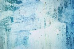 Old painted wall. The wall, painted in blue, covered with smears of white paint Stock Photo