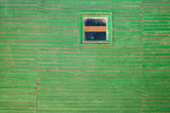 Old painted wooden wall. Background texture of old, weathered green wall with chipping paint and little window stock photos