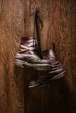 Old pair of brown boots hanging on a wall Royalty Free Stock Photo