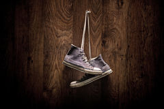 Old pair of denim snickers hanging on a wooden wall Royalty Free Stock Image