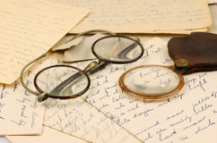 Old pair of glasses and a magnifying glass. On some old letters Royalty Free Stock Images