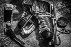 Old pair of mens skates with puck and stick. Royalty Free Stock Photography