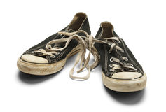 Old Pair of Shoes. Old Dirty Worn Pair of Canvas Shoes With Knoted Shoe Laces Isolated on White Background Stock Image