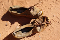 Old pair of shoes on sand Royalty Free Stock Photos