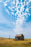 Old Pairie Cabin, Farm, Clouds. An old, abandoned vintage farm cabin sits on the empty, desolate prairie. A broken windmill is in the background. Surreal clouds Stock Images