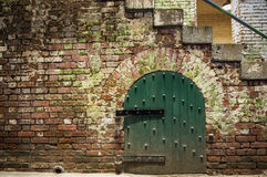 Old Pale Brick Wall With Gate. A weathered old brick wall with an old fashion green gate Stock Photos