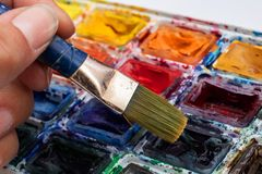 Old palette and brush with close up paints. Old palette and brush with closeup paints, background for text or texture stock photo