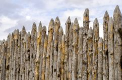 Old paling of sharpened logs on sky background. Old palisade of sharpened logs against the sky Stock Images