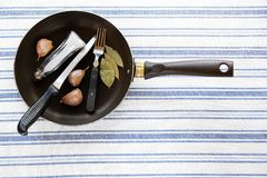 In an old pan are salt shaker, Cutlery, garlic and Bay leaf, on a striped linen towel, close-up. Home cooking. The concept of royalty free stock photos
