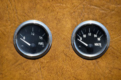 Old panel of instuments. Fuel gauge and voltmeter on vintae car instruments panel stock photos