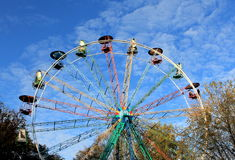 Old panorama wheel spinning. Old panorama wheel in autumn with yellowish trees and blue skies royalty free stock photos