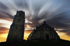 Old historic Paoay Church during sunrise with moving clouds Royalty Free Stock Image