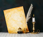 Old paper. With a candle and a quill pen royalty free stock image