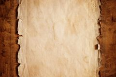 Old paper. Abstract grunge background - old broken paper on brown wooden board stock image