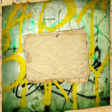 Old paper on the ancient graffiti wall Royalty Free Stock Photos